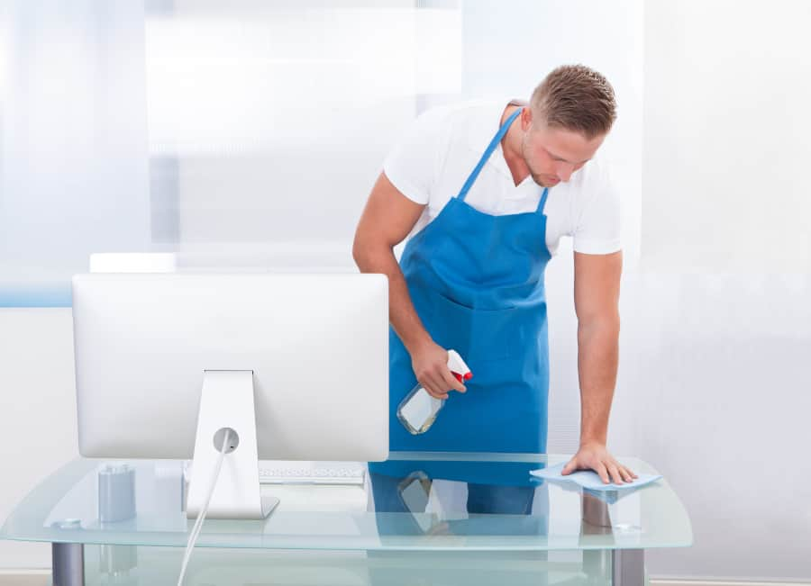 janitor cleaning glass desk